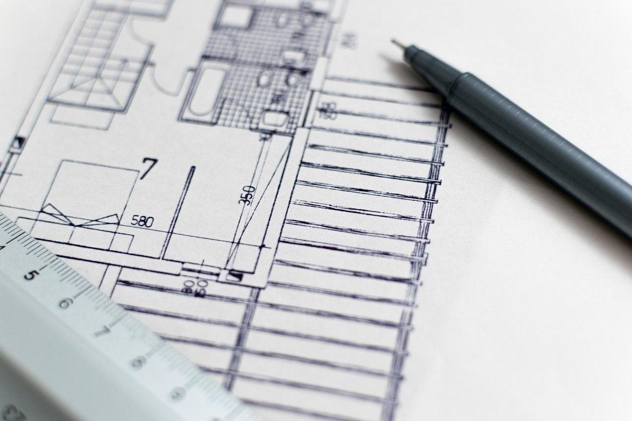 fotografia de uma Planta de arquitectura onde se pode ver uma caneta e uma régua pousadas em cima de um desenho técnico de uma divisão