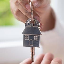 BQ Advogadas - direito civil imobiliario arrendamento - porta-chaves com formato de casa e uma chave. Está a ser segurado por uma mão e em posição de entrega
