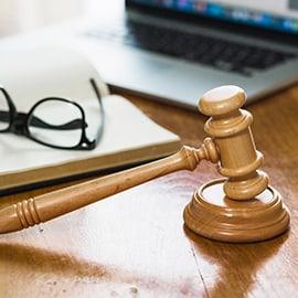 BQ Advogadas - direito penal - Martelo de madeira em cima da mesa, livro aberto com óculos em cima, computador portátil