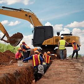 BQ Advogadas - direito trabalho - trabalhadores de obras numa vala aberta na terra, retro-escavadora