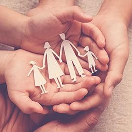 BQ Advogadas - direito familia - dois pares de mãos em concha, um por cima do outro, a segurar uma familia recortada em papel