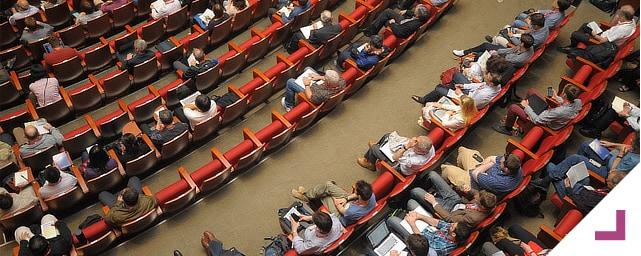 BQ Advogadas. Informação/Eventos. Auditório cheio de pessoas sentadas fotografado de cima.