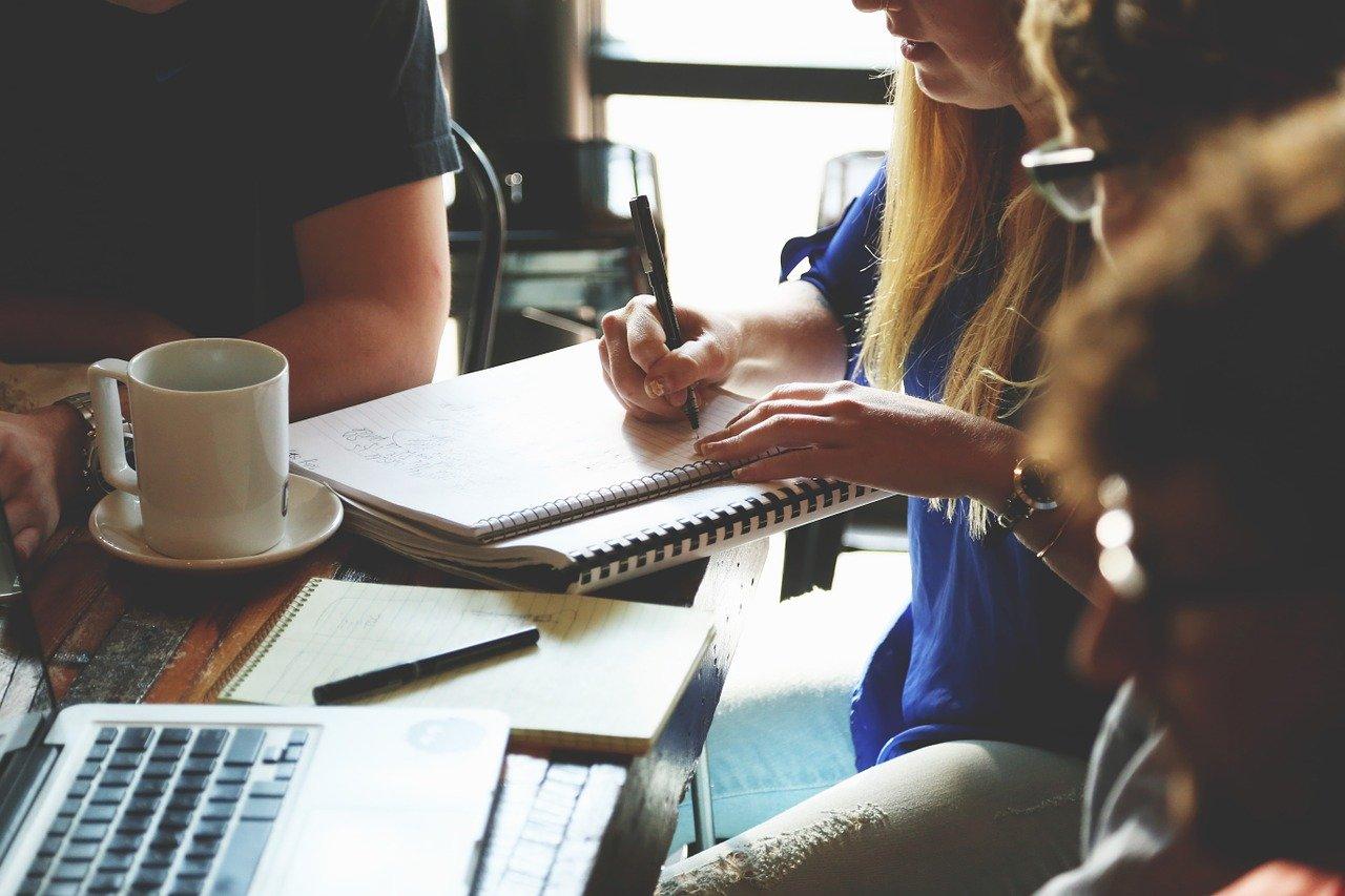 Sociedades por quotas: imagem de introdução onde se podem ver várias pessoas numa mesa, em reunião. Plano fechado. Portátil, caneca de café e blocos de notas em cima da mesa.